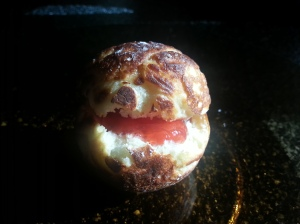 An aebleskive with strawberry jam in the center.